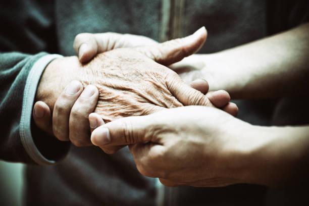 Elderly hand and caregiver
